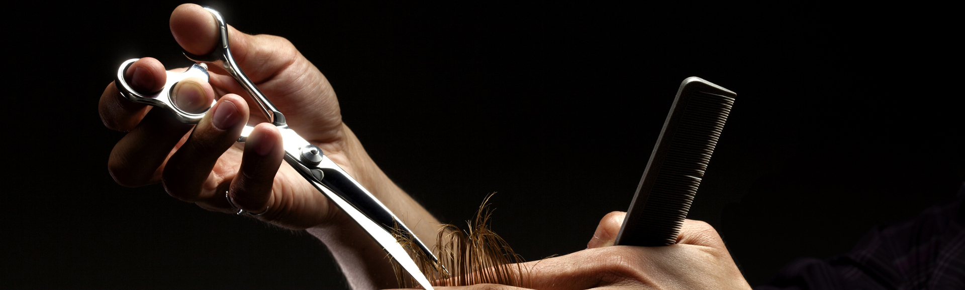 Studio shot on black of hairdresser's hands cutting red woman hair with professional scissors